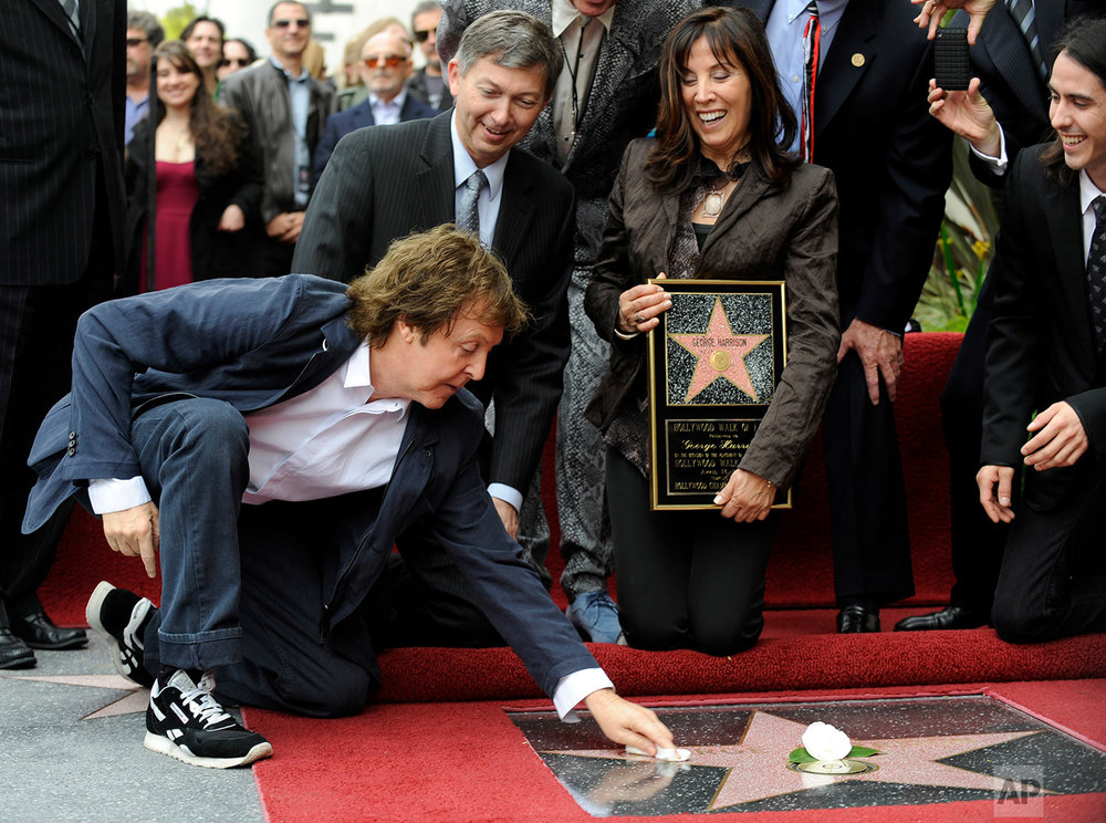 Paul McCartney, far left, dusts off the new star for his former Beatles bandmate George Harrison during a posthumous Hollywood Walk of Fame star dedication for Harrison in Los Angeles, Tuesday, April 14, 2009. Looking on from left to right are Leron Gubler, president/CEO of the Hollywood Chamber of Commerce, Harrison's wife Olivia and his son Dhani Harrison. (AP Photo/Chris Pizzello)