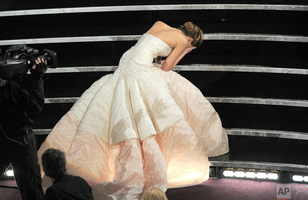 "Actress Jennifer Lawrence stumbles as she walks on stage to accept the award for best actress in a leading role for ""Silver Linings Playbook"" during the Oscars at the Dolby Theatre on Sunday Feb. 24, 2013, in Los Angeles.  (Photo by Chris Pizzello/Invision/AP)"
