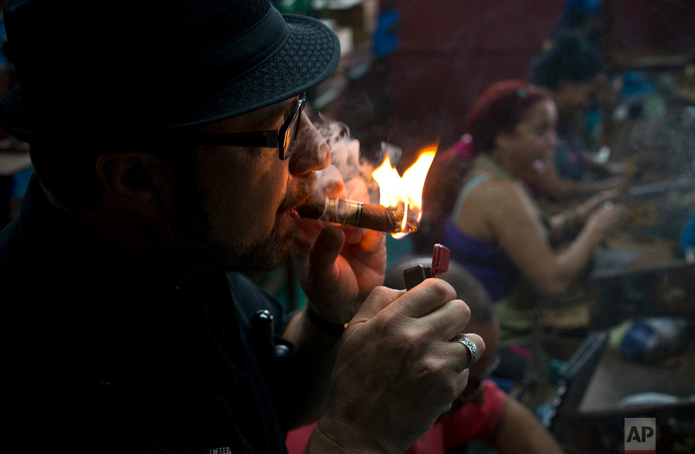 In this March 1, 2018 photo, tobacco enthusiast Paul Segal of California lights a cigar as rollers are seen working in the background, at La Corona cigar factory in Havana, Cuba. (AP Photo/Ramon Espinosa)
