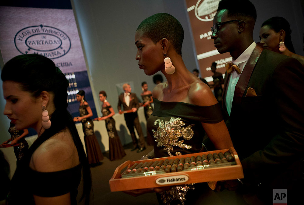 In this March 2, 2018 photo, models carry trays of aged cigars for guests, at a gala dinner of the 20th Cigar Festival in Havana, Cuba. (AP Photo/Ramon Espinosa)