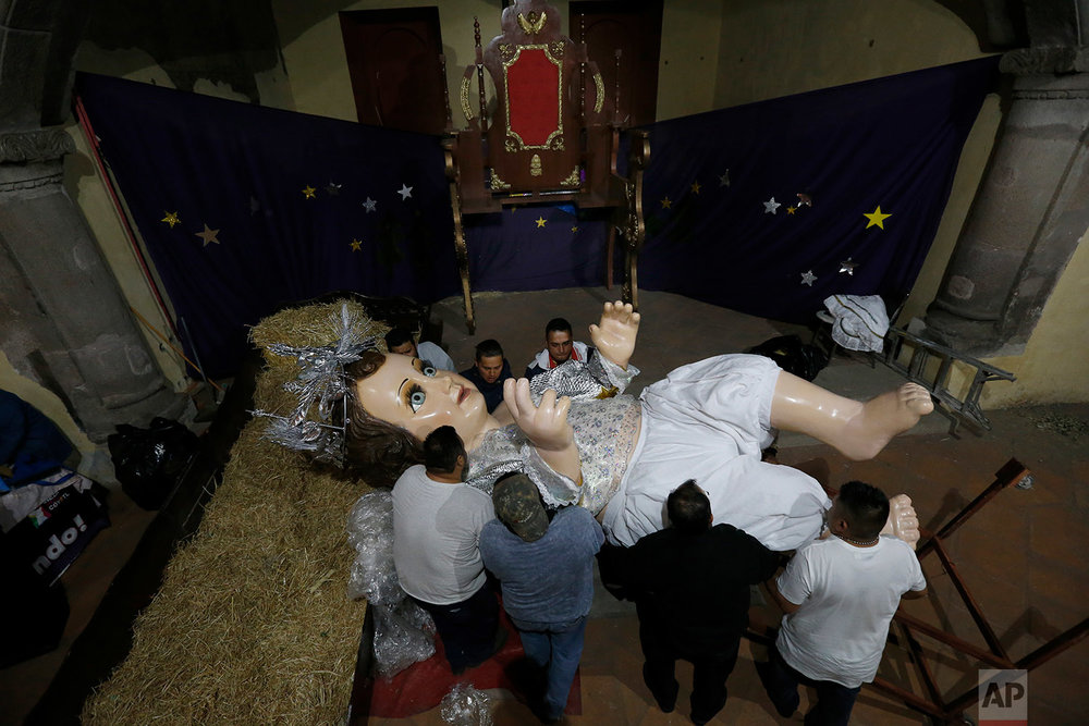 "In this Feb. 1, 2018 photo, parishioners dress a giant baby Jesus in preparation for ""Dia de la Candelaria"" or Candlemas Day, at the San Juan Bautista Parish, in Mexico City. (AP Photo/Marco Ugarte)"