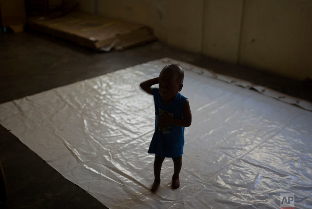 In this Feb. 2, 2018 photo, a boy stands on a tarp at the Foyer Notre Dame de la Nativite orphanage on the outskirts of Port-au-Prince, Haiti, where several children being adopted from the orphanage by U.S. families have been victims of alleged sexual abuse. (AP Photo/Dieu Nalio Chery)