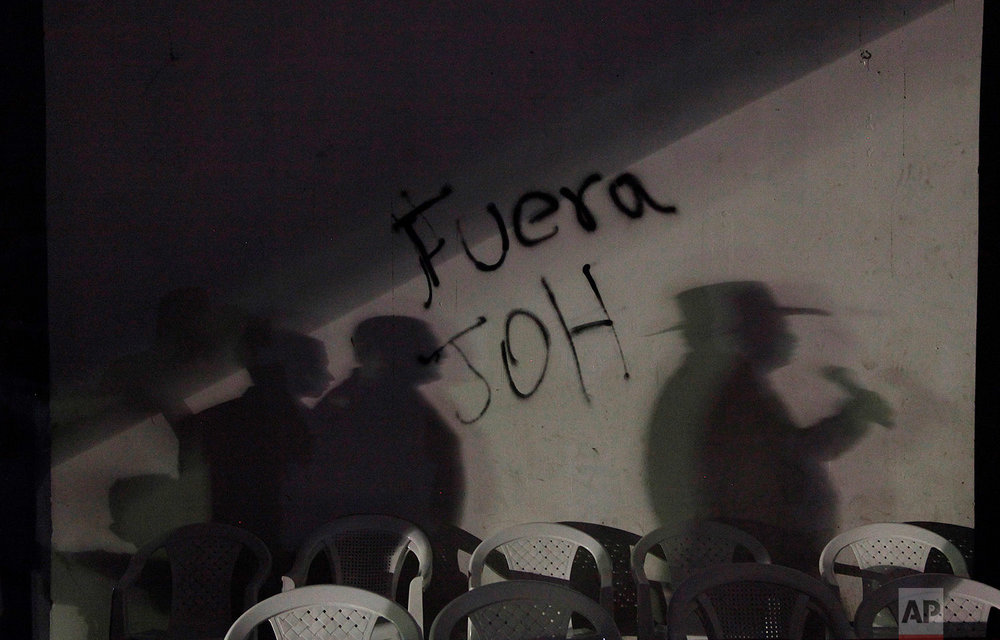 "In this Feb. 3, 2018 photo, a shadow of ousted Honduran President Manuel Zelaya is cast on a wall spray painted with a message that reads in Spanish: ""Get out JOH,"" referring to re-elected President Juan Orlando Hernandez, in Central Park, Tegucigalpa, Honduras. (AP Photo/Fernando Antonio)"
