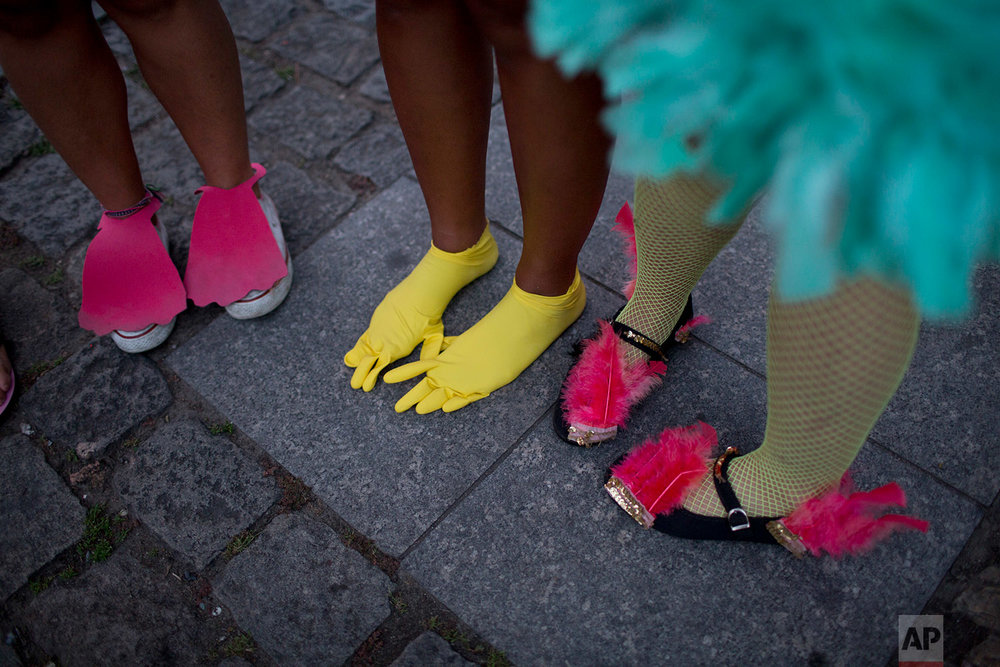 "In this Feb. 3, 2018 photo, a woman wears plastic, yellow gloves on her feet as part of her bird costume during the block party ""Maria vem com as outras,"" or ""Maria, join the other women,"" in Rio de Janeiro, Brazil. (AP Photo/Silvia Izquierdo)"