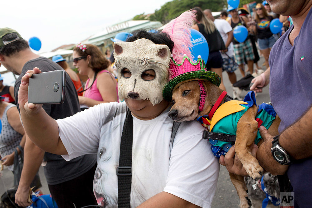 "In this Feb. 4, 2018 photo, a woman takes a selfie with Kaike the dog, both decked out in costumes for the ""Blocao"" dog carnival parade along Copacabana beach in Rio de Janeiro, Brazil. (AP Photo/Silvia Izquierdo)"