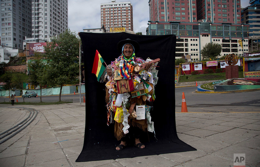 "In this Feb. 5, 2018 photo, Cornelio Colque Huanca, dressed as ""Ekeko,"" the god of prosperity, and the central figure of the Alasita Fair, poses for a portrait in front of a black curtain in La Paz, Bolivia. (AP Photo/Juan Karita)"