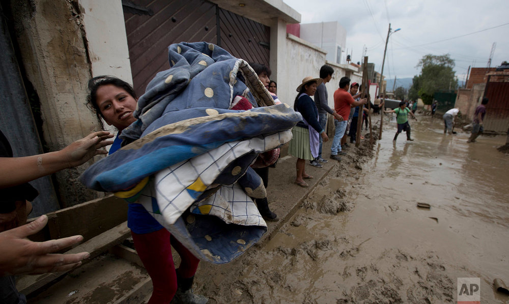 In this Feb. 7, 2018 photo, people salvage bedding from a flooded home in Tiquipaya near Cochabamba, Bolivia. (AP Photo/Juan Karita)