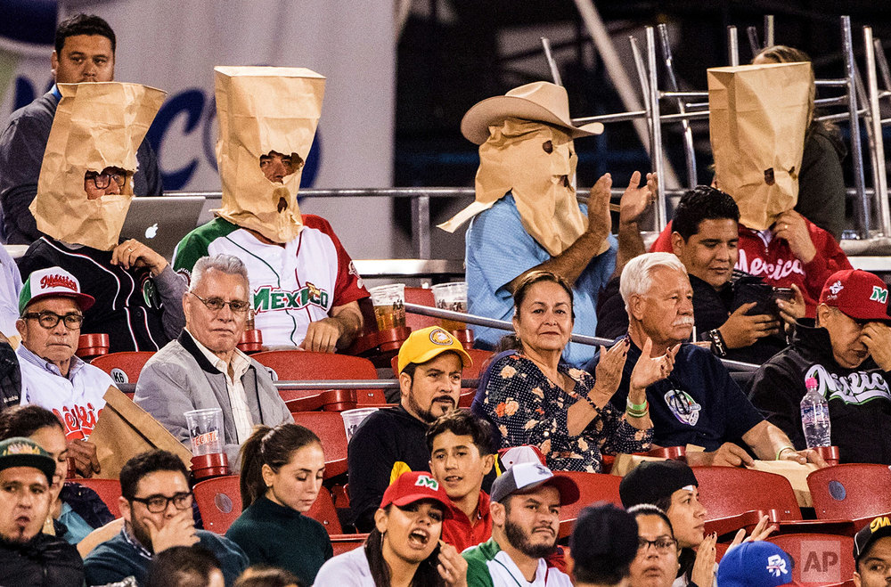 In this Feb. 6, 2018 photo, Mexico baseball fans wear paper bags over their heads during a Caribbean Series game between Dominican Republic's Aguilas Cibaenas and Mexico's Tomateros de Culiacan in Guadalajara, Mexico. (AP Photo/Luis Gutierrez)