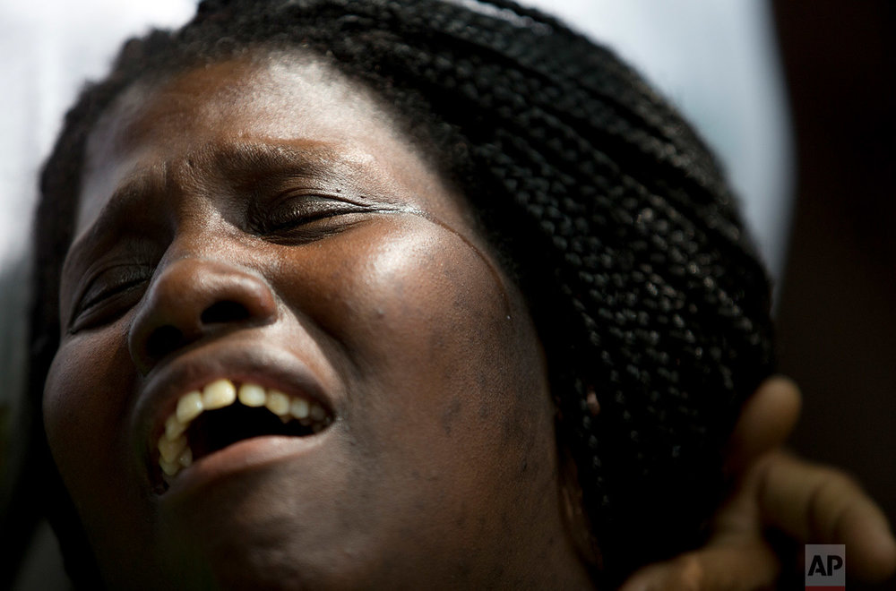 In this Feb. 8, 2018 photo, Wania de Moraes grieves for her 13-year-old son Jeremias Moraes da Silva, who was killed by a stray bullet, during his burial service in Rio de Janeiro, Brazil. (AP Photo/Silvia Izquierdo)