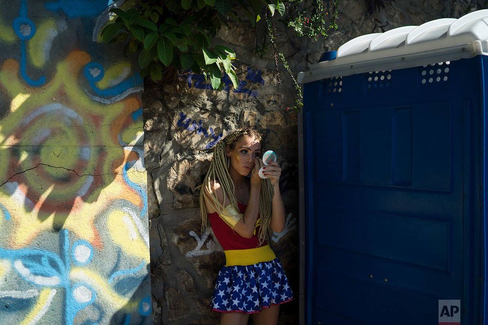 In this Feb. 9, 2018 photo, a woman wearing a Wonder Woman costume retouches her make-up during the Carmelitas street party in Rio de Janeiro, Brazil. (AP Photo/Leo Correa)