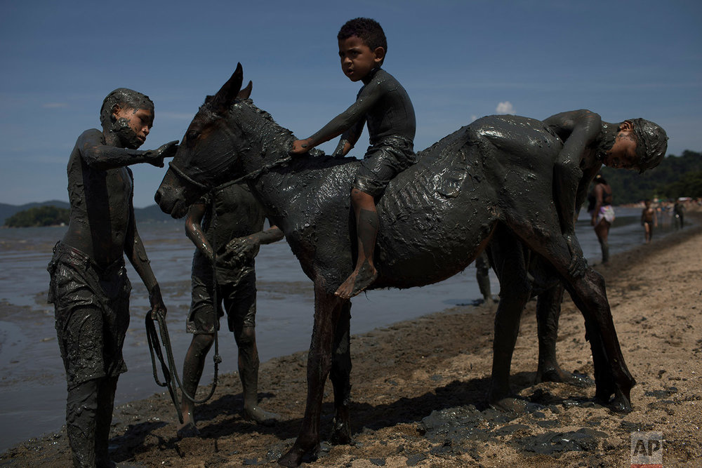 "In this Feb. 9, 2018 photo, kids cover a horse with mud as they take part in the traditional ""Bloco da Lama"" or ""Mud Block"" carnival party in Paraty, Brazil. (AP Photo/Leo Correa)"