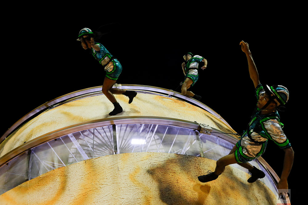 In this Feb. 12, 2018 photo, performers from the Vila Isabel samba school run as they hang from a sphere on a float during Carnival celebrations at the Sambadrome in Rio de Janeiro, Brazil. (AP Photo/Leo Correa)