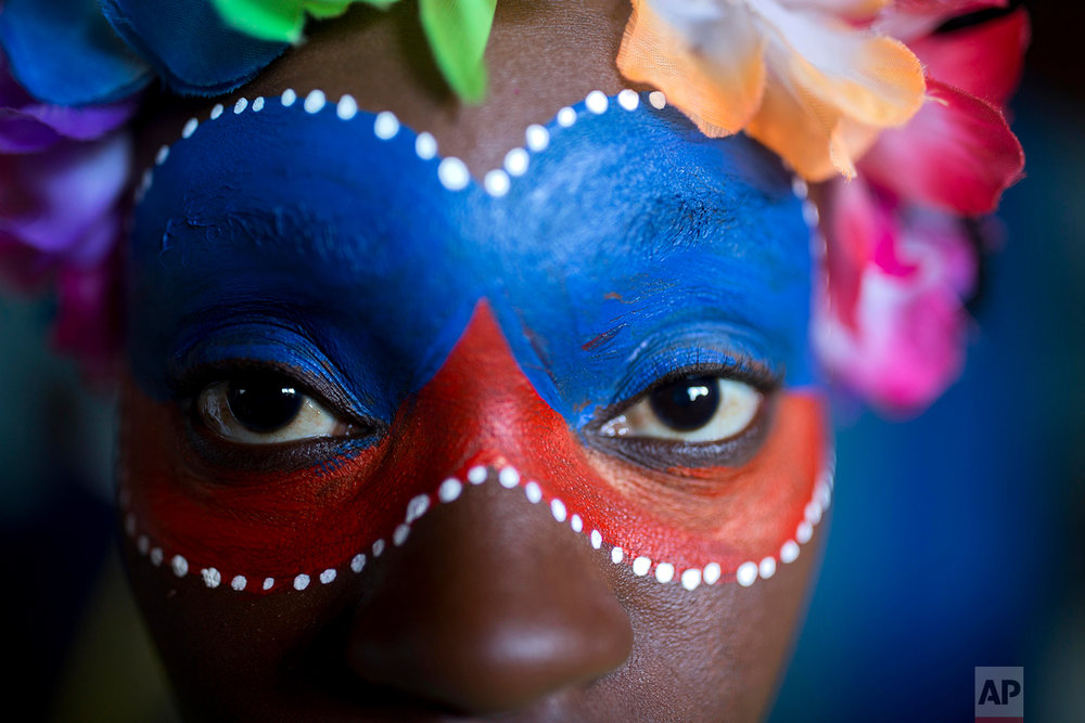 In this Feb. 12, 2018 photo, a reveler poses for a photo before the start of the Carnival parade in Port-au-Prince, Haiti. ( AP Photo/Dieu Nalio Chery)