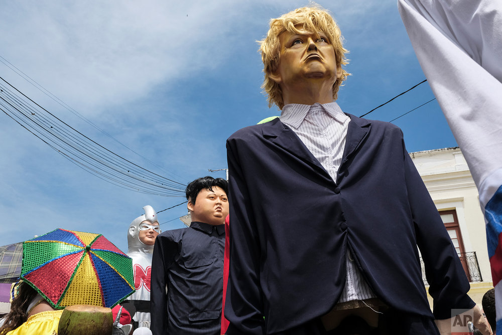 In this Feb. 12, 2018 photo, giant dolls depicting U.S. President Donald Trump and North Korean leader Kim Jong-un, parade past during Carnival in Olinda, in the Brazilian state of Pernambuco. (AP Photo/Diego Herculano)