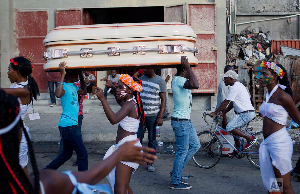 In this Feb. 12, 2018 photo, men carry an empty coffin past a Carnival parade in Port-au-Prince, Haiti. (AP Photo/Dieu Nalio Chery)