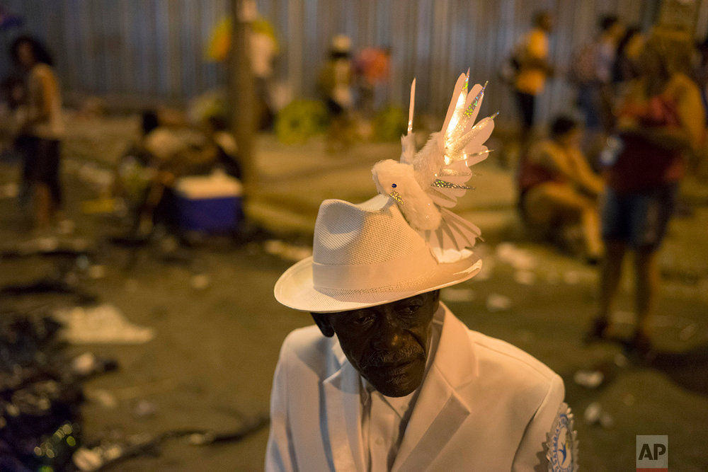 In this Feb. 13, 2018 photo, Jorge Rozario, 64, a member from Beija Flor samba school, gathers with some friends as Carnival celebrations wind down, at the Sambadrome in Rio de Janeiro, Brazil.  (AP Photo/Leo Correa)
