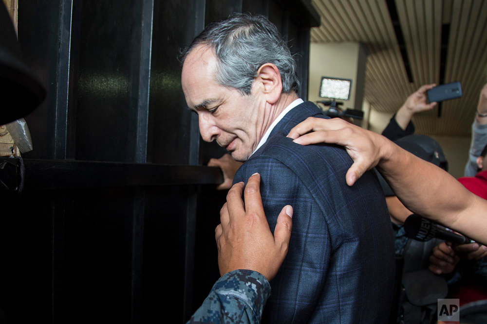 In this Feb. 13, 2018 photo, police officers pat down former Guatemalan President Alvaro Colom before escorting him into a court hearing in Guatemala City. (AP Photo/Luis Soto)
