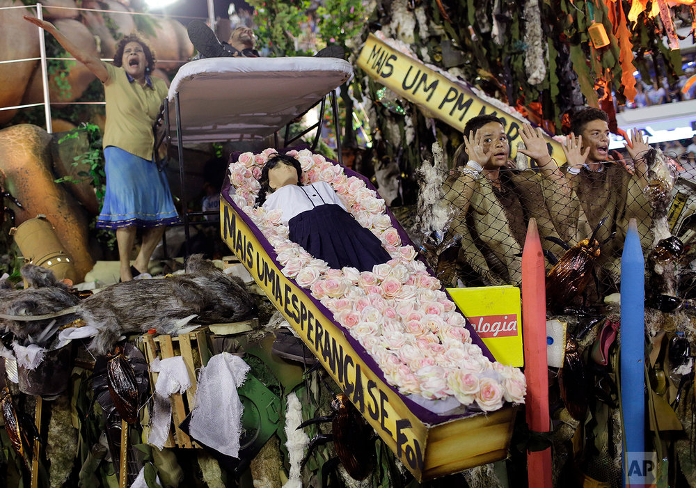 In this Feb. 13, 2018 photo, members from the Beija Flor samba school perform showing a coffin containing a doll representing a dead student during Carnival celebrations at the Sambadrome in Rio de Janeiro Brazil. (AP Photo/Silvia Izquierdo)