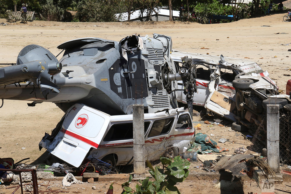 In this Feb. 17, 2018 photo, a downed helicopter sits on its side on top of a van, in Santiago Jimitepec, Oaxaca state, Mexico. The military helicopter carrying officials assessing damage from the Friday's earth quake crashed killing 13 people and injuring 15, all of them on the ground. (AP Photo/Luis Alberto Cruz Hernandez)