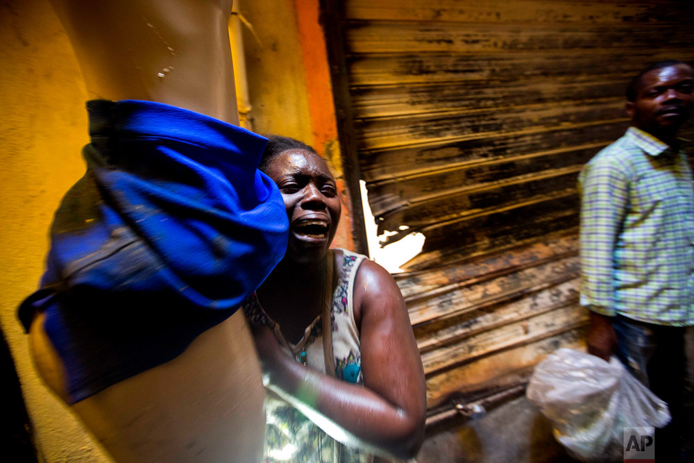 In this Feb. 18, 2018 photo, a vendor salvaging her mannequin wearing a skirt cries as she runs away from her stall burning during a massive fire at the biggest clothing market in Port-au-Prince, Haiti. (AP Photo/Dieu Nalio Chery)