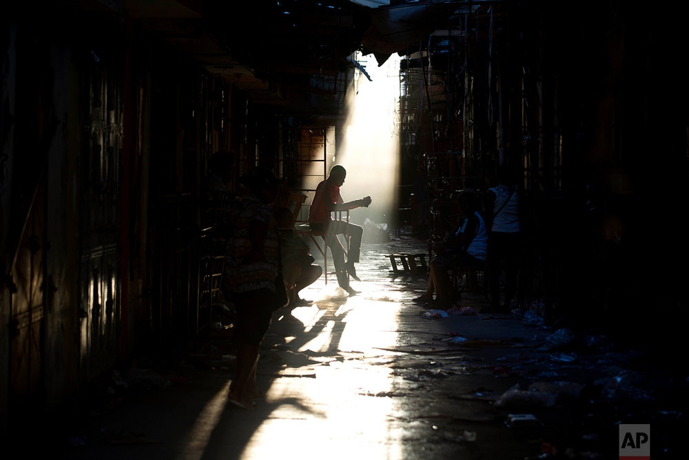 In this Feb. 19, 2018 photo, a vendor sits inside the burned ruins of a clothing market that was engulfed in flames a day before, in Port-au-Prince, Haiti. (AP Photo/Dieu Nalio Chery)