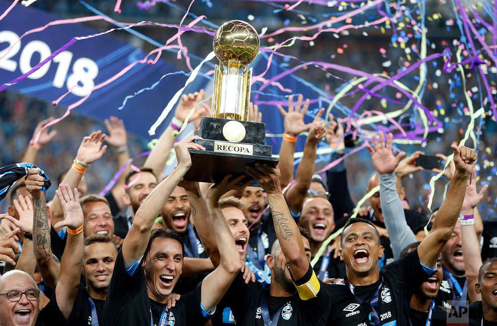 In this Thursday, Feb. 22, 2018 photo, Geromel of Brazil's Gremio holds up his team's trophy after they defeated Argentina's Independiente at the Recopa Sudamericana final soccer match, in Porto Alegre, Brazil. (AP Photo/Andre Penner)