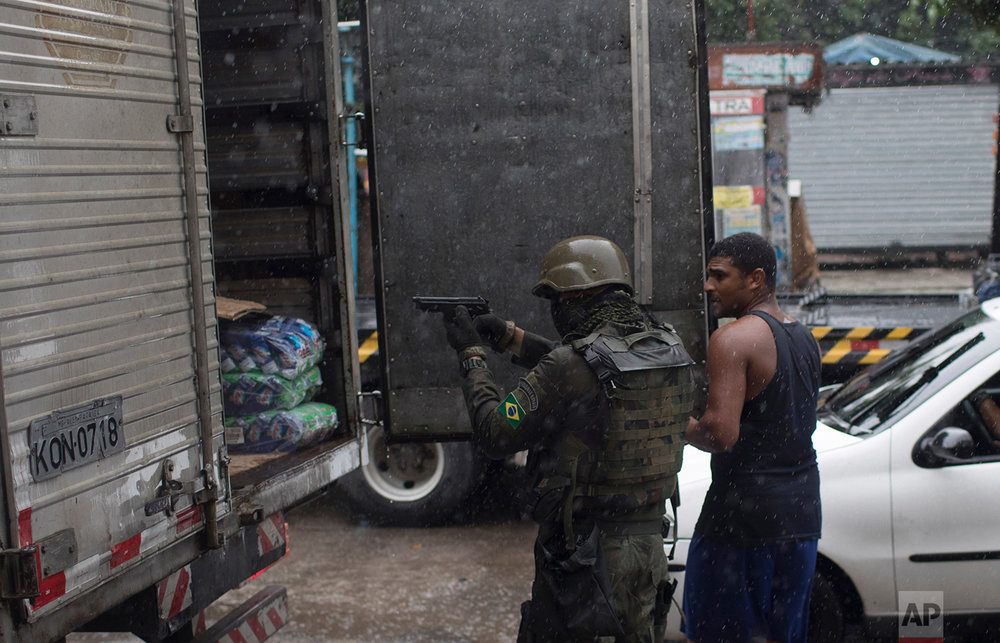 In this Feb. 23, 2018 photo, a soldier takes position as a driver opens the back of his trailer during a spot inspection at a checkpoint at the Vila Kennedy slum in Rio de Janeiro, Brazil. (AP Photo/Leo Correa)