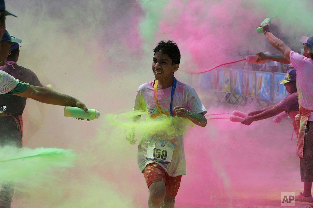 In this Feb. 24, 2018 photo, a boy doused with colored powder competes in the Color Run in Canete Peru. (AP Photo/Martin Mejia)