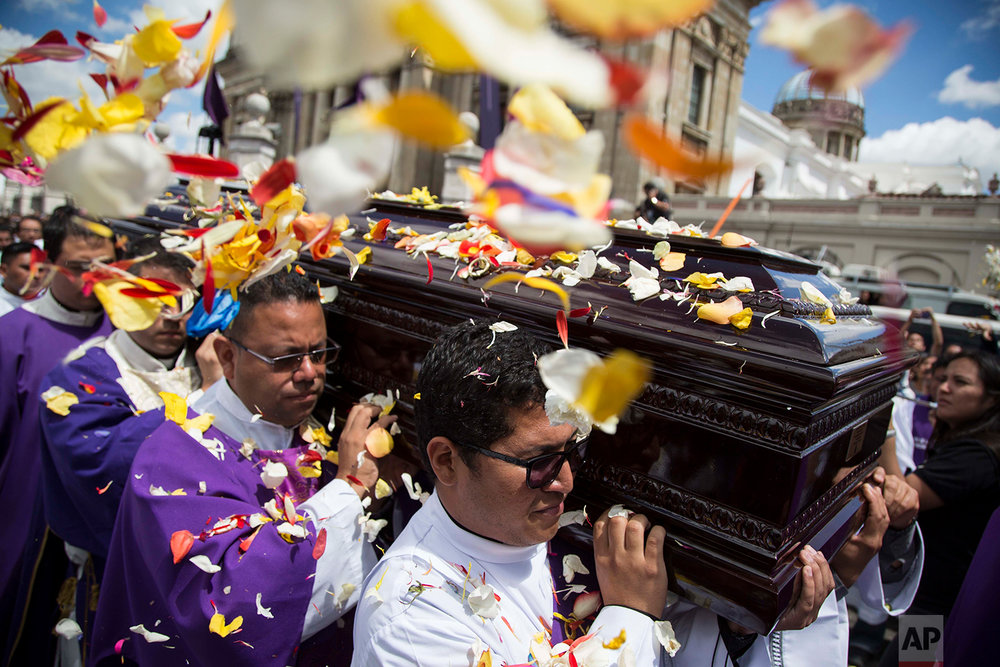 In this Feb. 27, 2018 photo, flower petals land on the coffin containing the remains of the late Archbishop Oscar Julio Vian Morales during his funeral procession outside the Metropolitan Cathedral in Guatemala City. (AP Photo/Luis Soto)