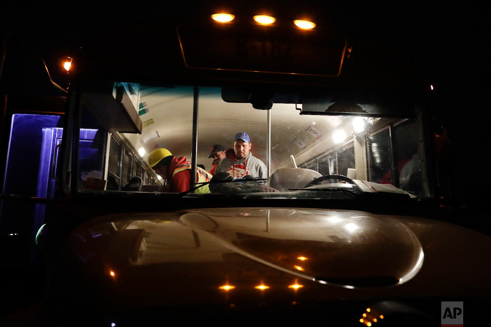 In this March 6, 2018 picture, farmworker Santiago Martinez, of Mexicali, Mexico, right, exits a bus as it arrives at a cabbage field ready for harvest, before dawn outside of Calexico, Calif. (AP Photo/Gregory Bull)