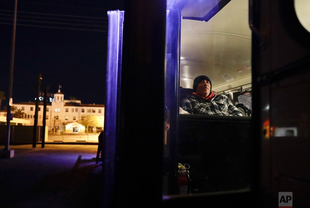 In this March 6, 2018 picture, farmworker Jose Angel Valenzuela rests as he waits before dawn in a bus that will take him and his crew from the border in Calexico, Calif, to a cabbage field ready for harvest outside of town. (AP Photo/Gregory Bull)