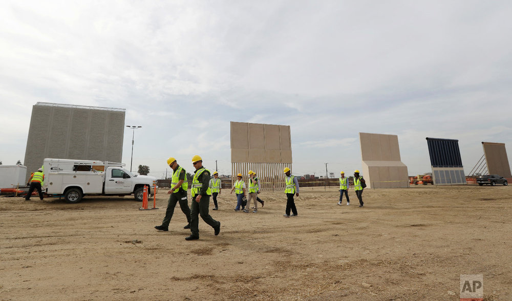 In this Oct. 19, 2017 photo, people pass border wall prototypes as they stand near the border with Tijuana, Mexico, in San Diego. (AP Photo/Gregory Bull)