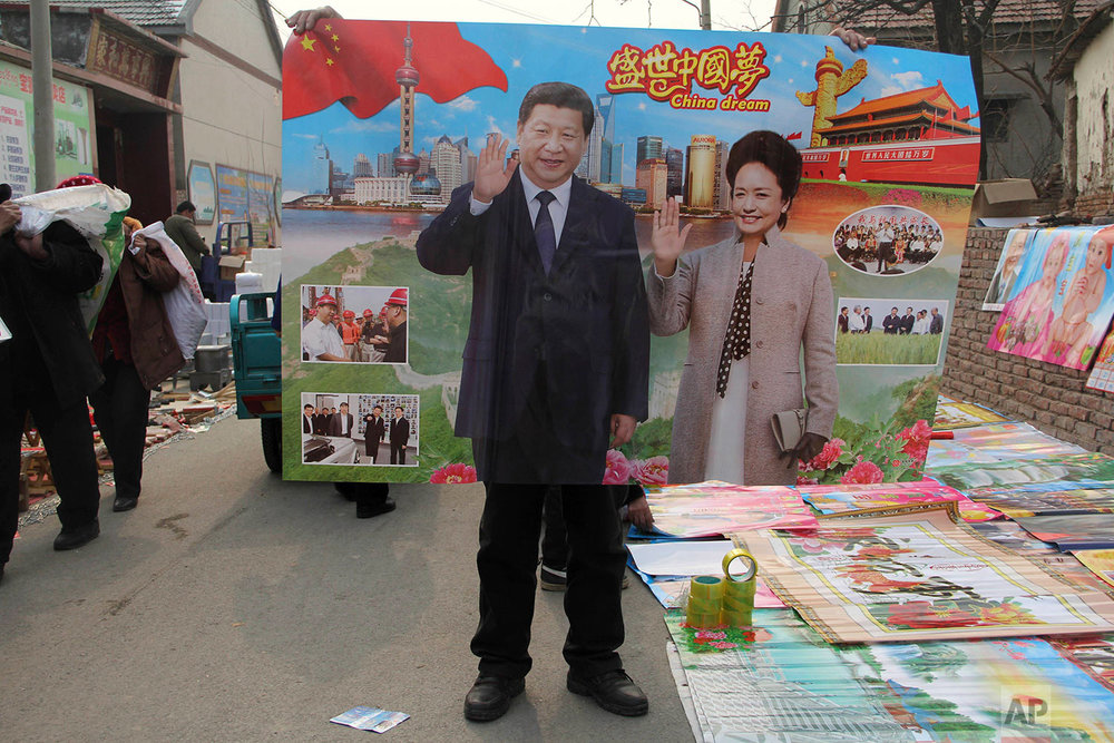 In this Jan. 28, 2016, photo, a vendor holds up a poster of Chinese President Xi Jinping and First Lady Peng Liyuan in a rural market during Chinese New Year season when locals traditionally paste new posters on the walls of their home in Binzhou in eastern China's Shandong province. Xi, poised to rule over China indefinitely, is at the center of the Communist Party's most colorful efforts to build a cult of personality since the death of the founder of the People's Republic, Mao Zedong, in 1976. (Chinatopix Via AP)