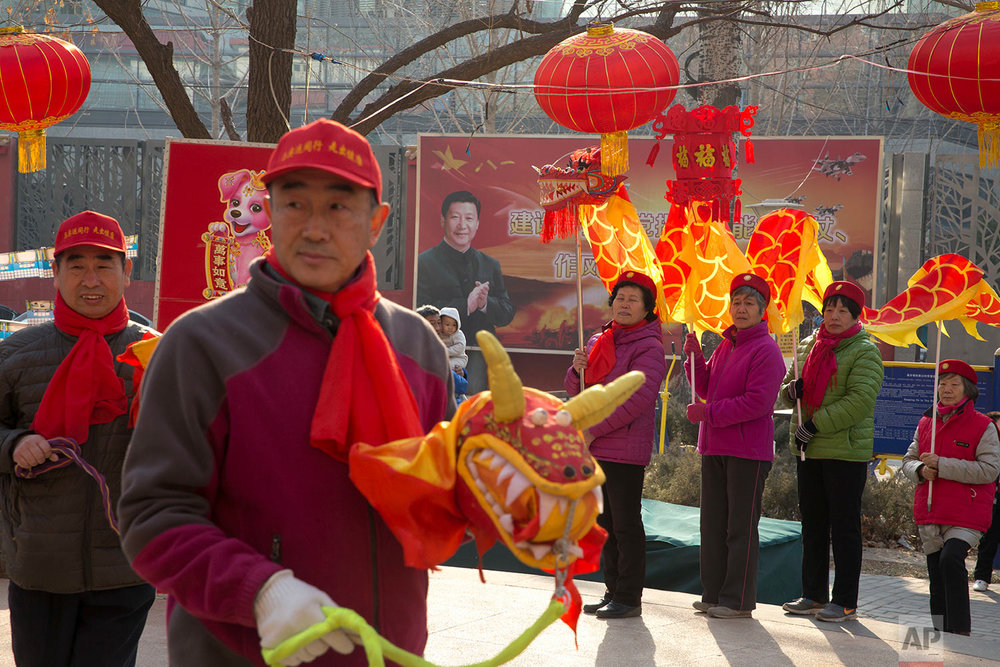 In this Friday, March 2, 2018, photo, residents celebrate lantern festival to mark the end of winter near a mural depicting Chinese President Xi Jinping in a residential compound for retired soldiers in Beijing. Xi, poised to rule over China indefinitely, is at the center of the Communist Party's most colorful efforts to build a cult of personality since the death of the founder of the People's Republic, Mao Zedong, in 1976. (AP Photo/Ng Han Guan)