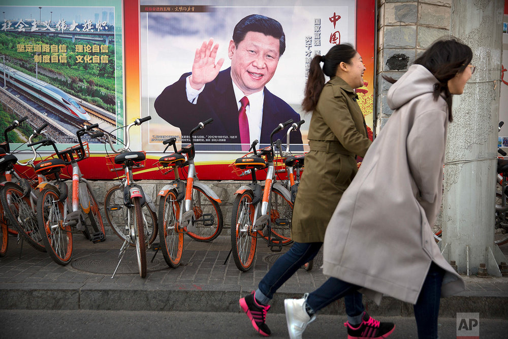In this Friday, March 2, 2018, photo residents walk past a poster showing Chinese President Xi Jinping in Beijing. Xi, poised to rule over China indefinitely, is at the center of the Communist Party's most colorful efforts to build a cult of personality since the death of the founder of the People's Republic, Mao Zedong, in 1976. (AP Photo/Mark Schiefelbein)