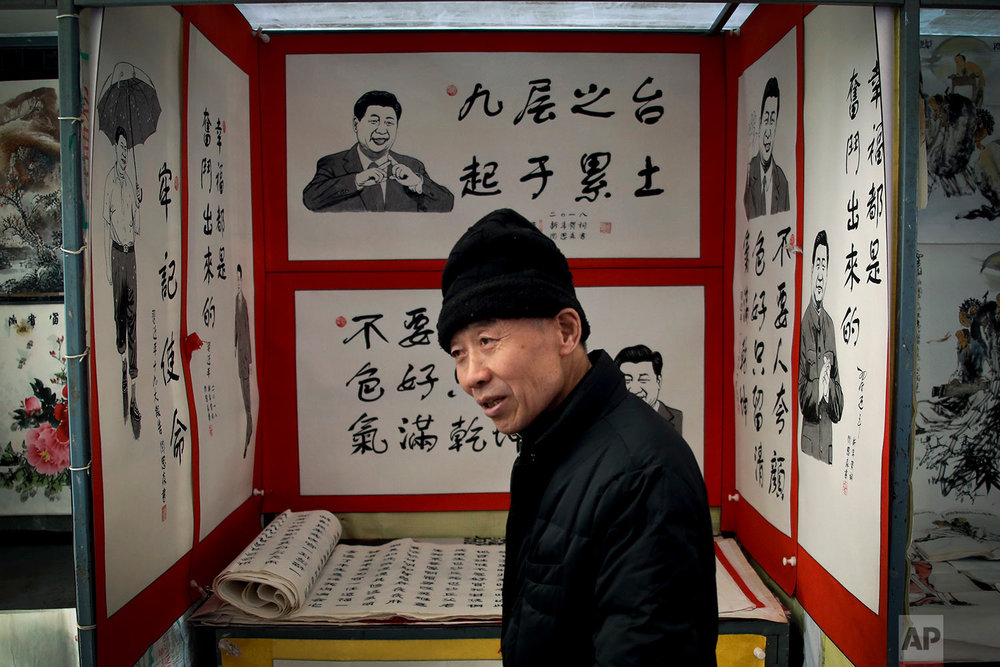 In this Thursday, March 1, 2018, photo, a man chats with his friend in front of posters featuring drawings of Chinese President Xi Jinping and his quotes on display for sale at a market in Beijing. Xi, poised to rule over China indefinitely, is at the center of the Communist Party's most colorful efforts to build a cult of personality since the death of the founder of the People's Republic, Mao Zedong, in 1976. (AP Photo/Andy Wong)
