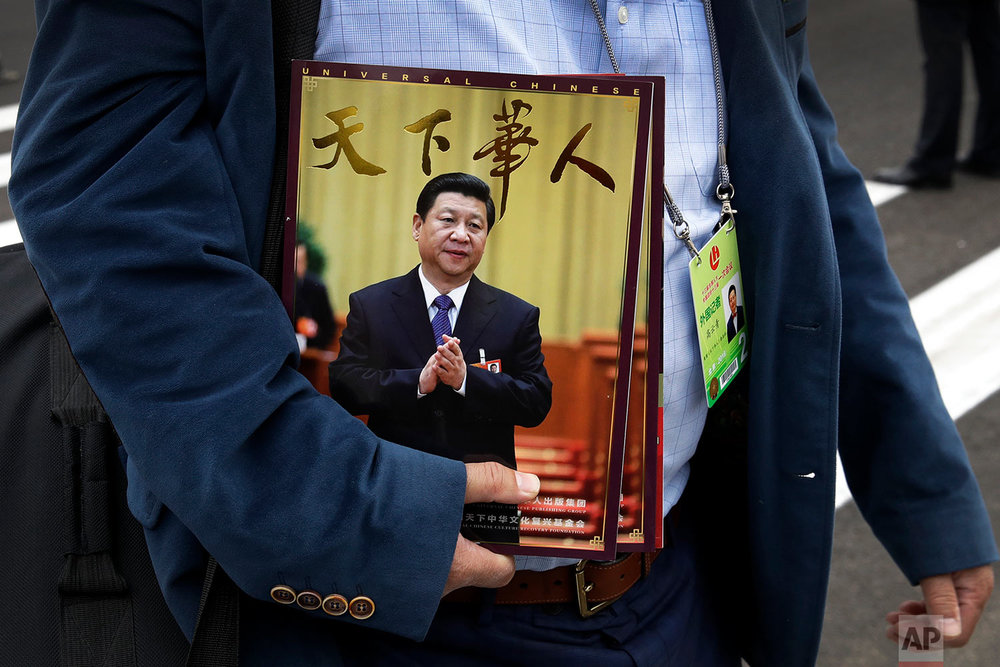 In this Saturday, March 3, 2018, photo, a journalist carrying magazines featuring Chinese President Xi Jinping on their front cover arrives for the opening of the Chinese People's Political Consultative Conference (CPPCC) at the Great Hall of the People in Beijing. Xi, poised to rule over China indefinitely, is at the center of the Communist Party's most colorful efforts to build a cult of personality since the death of the founder of the People's Republic, Mao Zedong, in 1976. (AP Photo/Andy Wong)