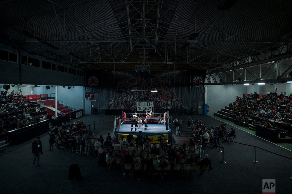 In this photo dated Saturday, Feb. 24, 2018, people watch wrestlers Darkmundo and Alex Legrand fighting during a wrestling charity gala in Ivry-sur-Seine, south of Paris, France. (AP Photo/Kamil Zihnioglu)