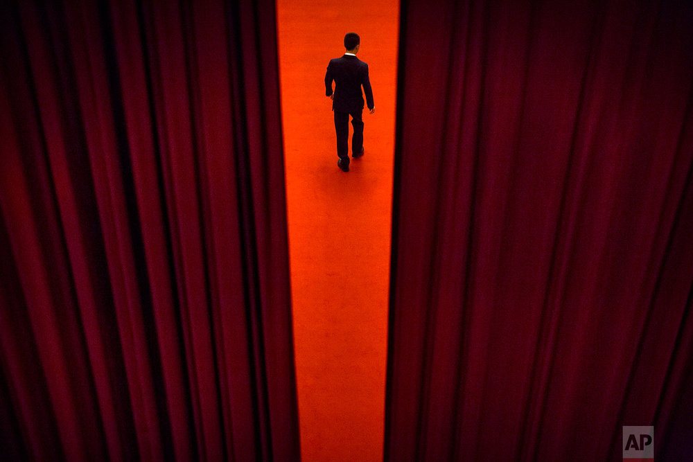 In this Thursday, March 8, 2018 photo, a security official walks through a curtained-off area during a plenary session of the Chinese People's Political Consultative Conference (CPPCC) at the Great Hall of the People in Beijing.  (AP Photo/Mark Schiefelbein)