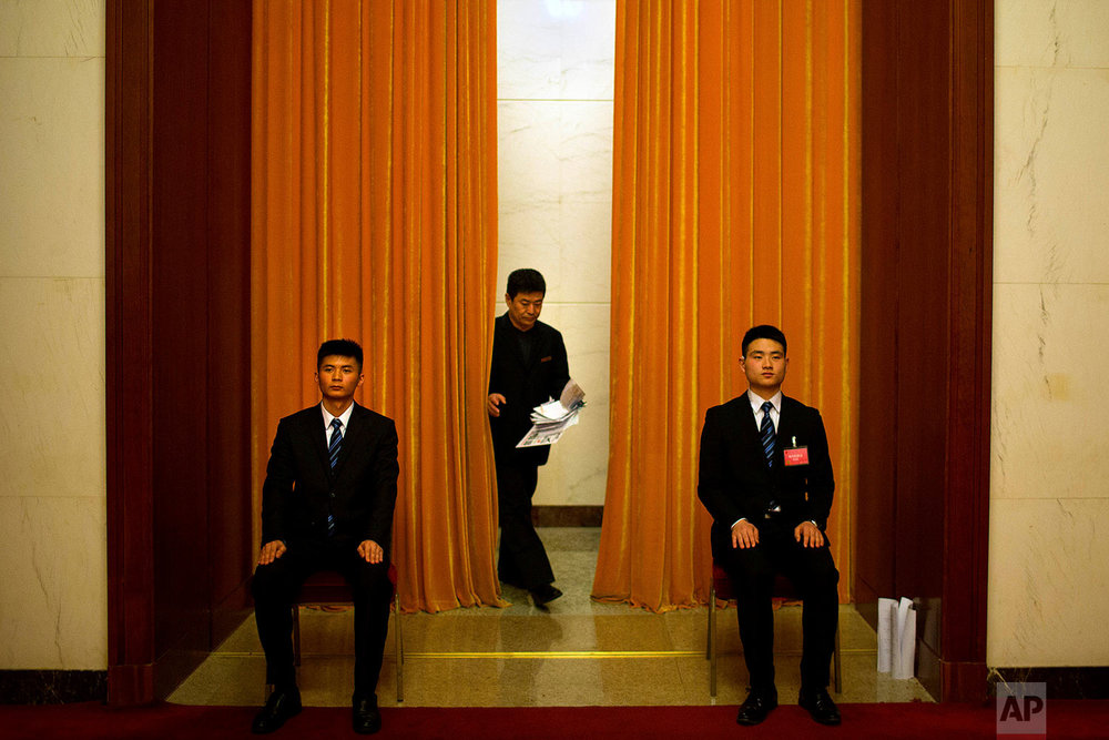 In this Tuesday, March 6, 2018 photo, an official walks out from behind a curtained-off area at the Great Hall of the People in Beijing. (AP Photo/Mark Schiefelbein)