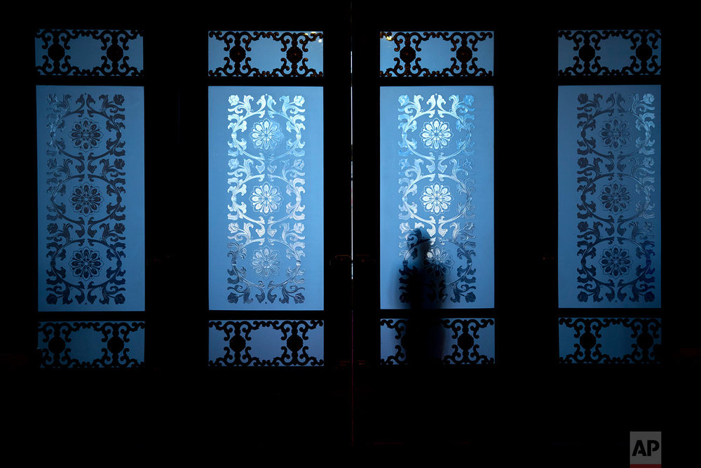 In this Friday, March 2, 2018 photo, a security official is silhouetted as he stands behind frosted glass doors at the Great Hall of the People in Beijing. (AP Photo/Mark Schiefelbein)