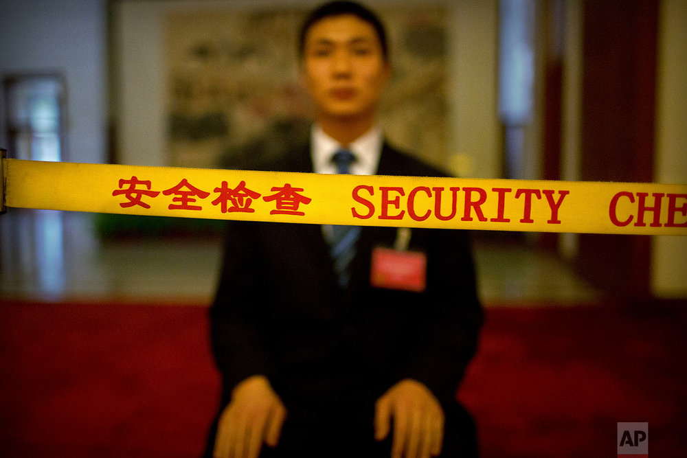 In this Friday, March 9, 2018 photo, a security official sits behind a rope line as he guards a corridor at the Great Hall of the People during a plenary session of China's National People's Congress (NPC) in Beijing. (AP Photo/Mark Schiefelbein)