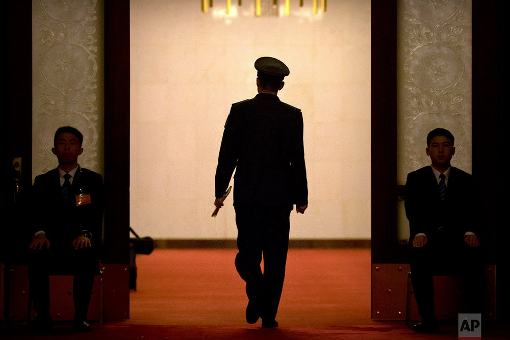 In this Friday, March 9, 2018 photo, a military officer walks through a door flanked by a pair of security officials during a plenary session of China's National People's Congress (NPC) at the Great Hall of the People in Beijing. (AP Photo/Mark Schiefelbein)