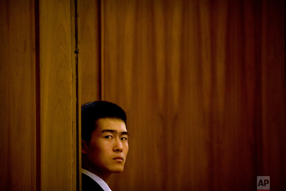 In this Friday, March 9, 2018 photo, a security official stands guard at a door during a plenary session of China's National People's Congress (NPC) at the Great Hall of the People in Beijing. (AP Photo/Mark Schiefelbein)