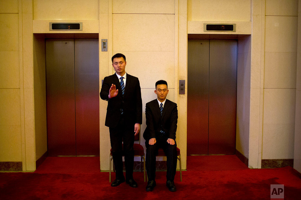 In this Tuesday, March 6, 2018 photo, security officials gesture as they stand guard at a bank of elevators at the Great Hall of the People in Beijing. (AP Photo/Mark Schiefelbein)