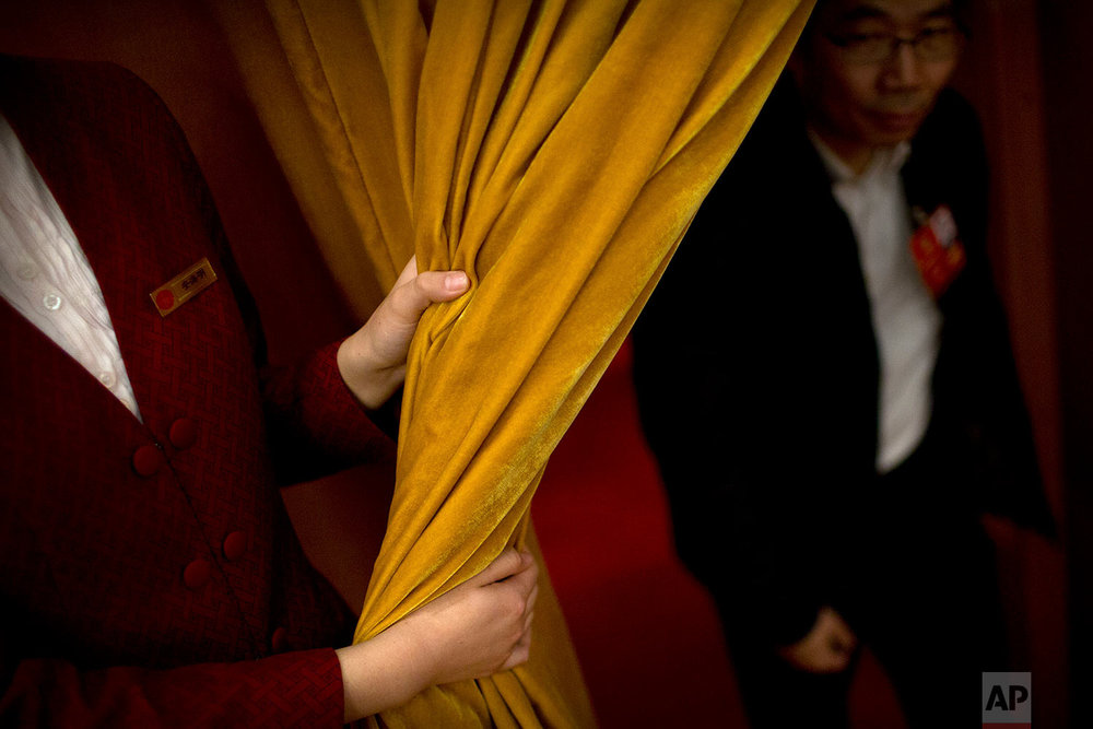 In this Friday, March 9, 2018 photo, an attendant pulls back a curtain for a delegate during a plenary session of China's National People's Congress (NPC) at the Great Hall of the People in Beijing. (AP Photo/Mark Schiefelbein)