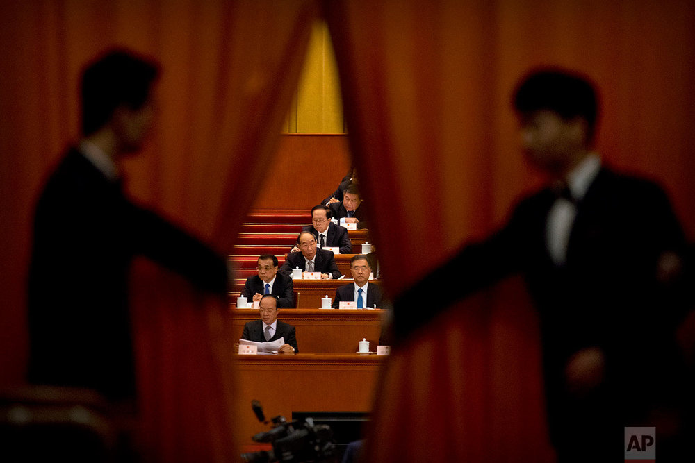 In this Friday, March 9, 2018 photo, ushers pull back a curtain as Chinese Premier Li Keqiang, second row left, and Politburo Standing Committee member Wang Yang, second row at right, attend a plenary session of China's National People's Congress (NPC) at the Great Hall of the People in Beijing. (AP Photo/Mark Schiefelbein)