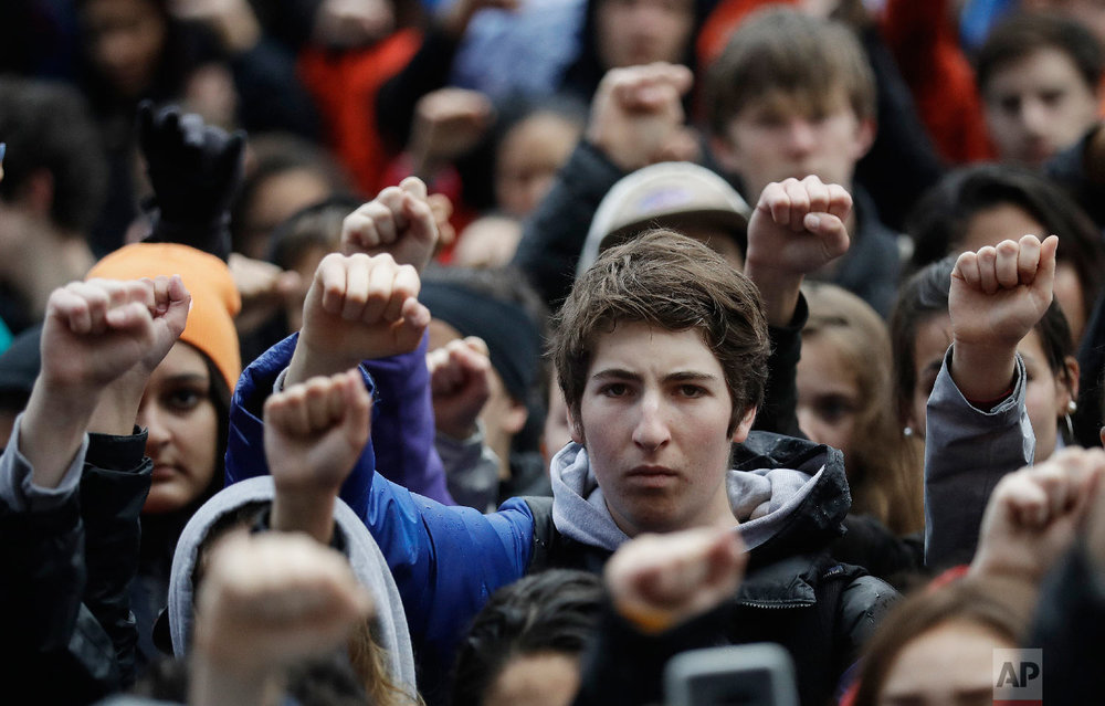 Demonstrators raise their fists in the air during a student-led march against gun violence at the Civic Center Plaza Wednesday, March 14, 2018, in San Francisco, one month after the deadly shooting inside a high school in Parkland, Fla. (AP Photo/Marcio Jose Sanchez)