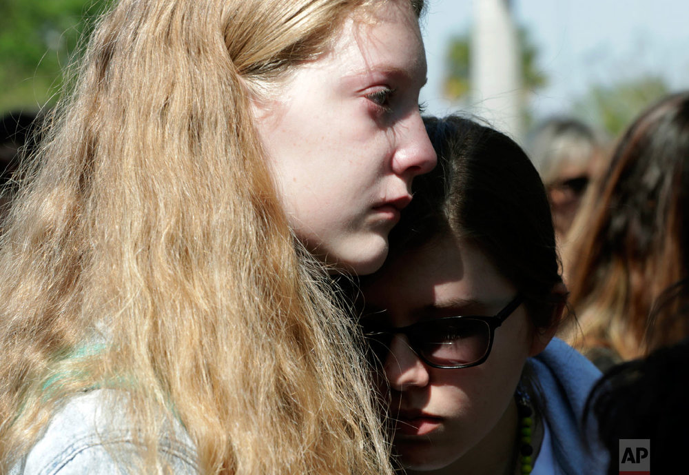 Hannah Grinbank, 13, left, cries as she and Morley Prager, right, listen to students speak at Pine Trails Park, as part of a nationwide protest against gun violence, Wednesday, March 14, 2018, in Parkland, Fla.  (AP Photo/Lynne Sladky)
