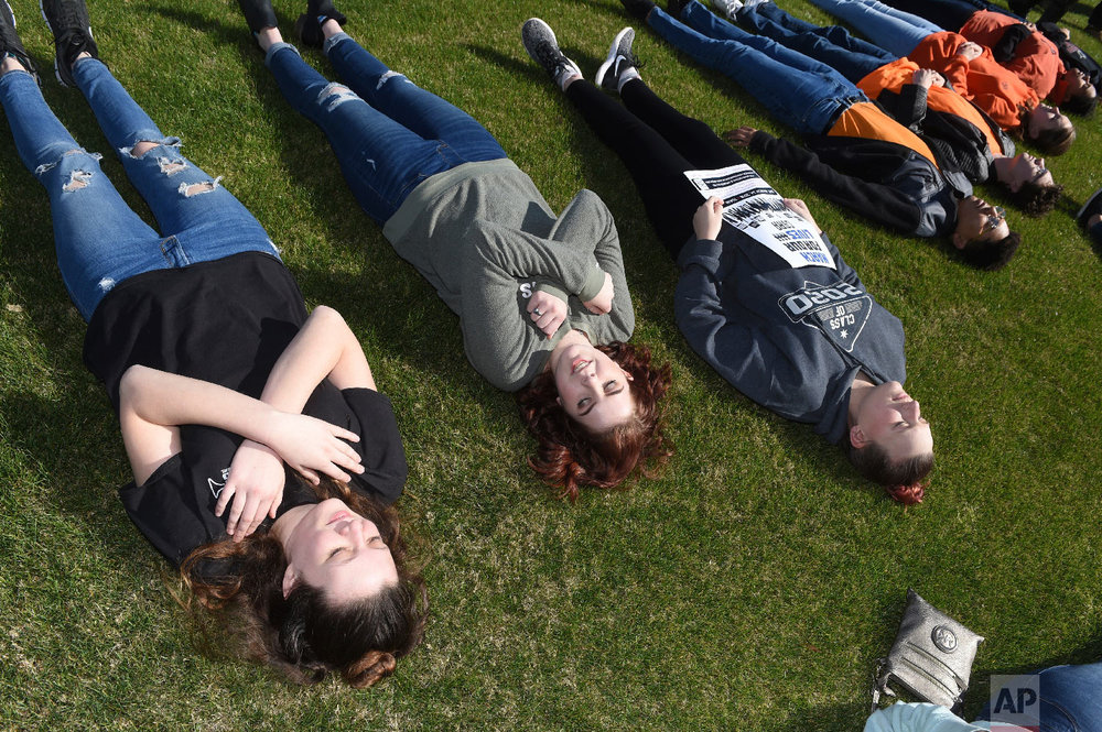 Students lie in the grass outside Congressman Rick Allen's office during a walkout to protest gun violence, Wednesday, March 14, 2018 in Augusta, Ga., one month after the deadly shooting inside a high school in Parkland, Fla. (Michael Holahan/The Augusta Chronicle via AP)